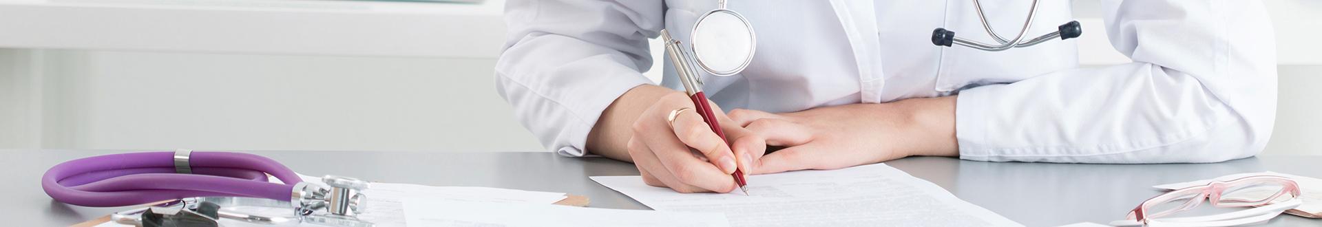 Lekarz piszący na kartce papieru